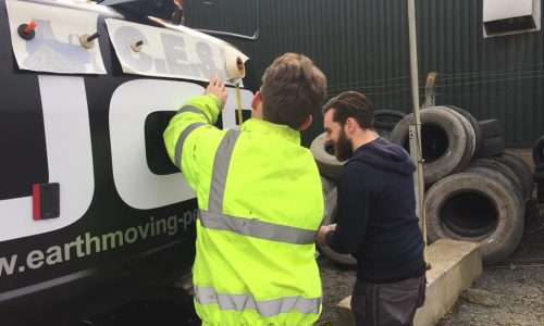 Employees adding Company Branding to JCB Vehicle